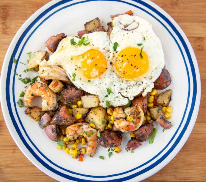 overhead shot of low country breakfast on a blue rimmed white plate