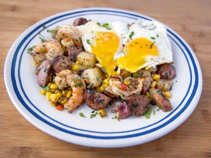 shrimp and andouille mixture with two sunny side up eggs with the yolks running on the misture
