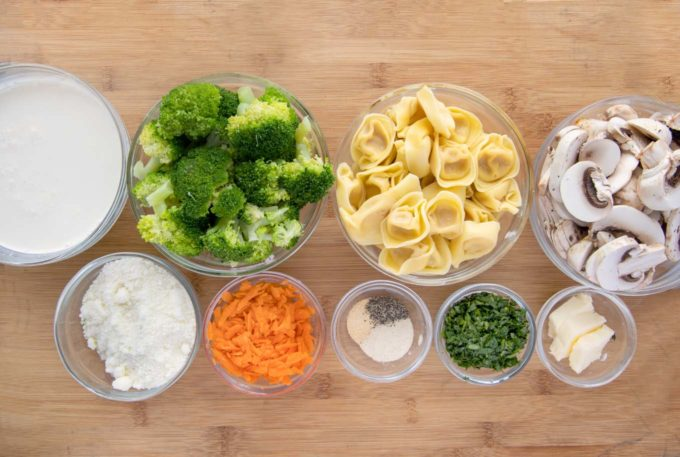 ingredients to make tortellini and broccoli in glass bowls