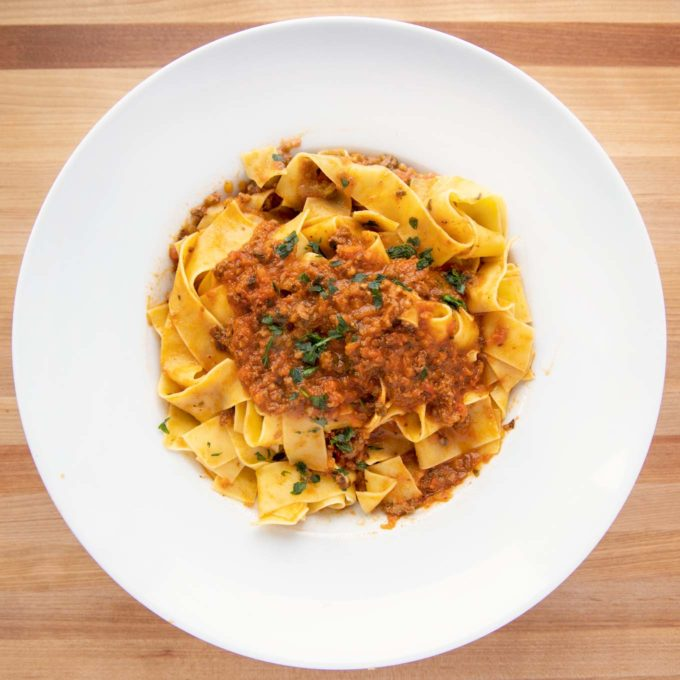 overhead shot of a white bowl with pappardelle bolognese