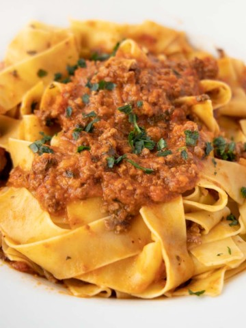 white bowl of pappardelle noodles with bolognese sauce