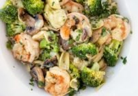 Shrimp and broccoli over linguine in a white bowl