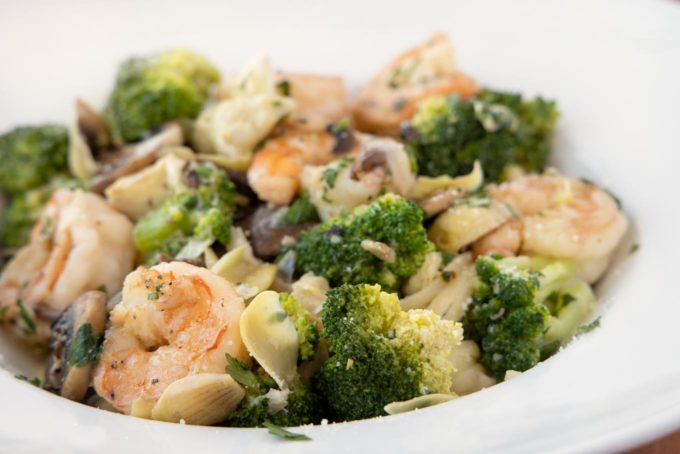 side view of shrimp and broccoli in a white bowl