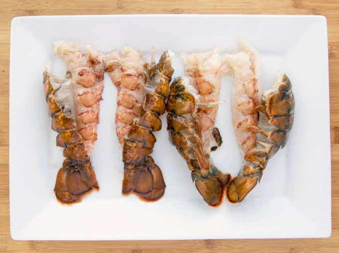 split lobster tails on a white platter