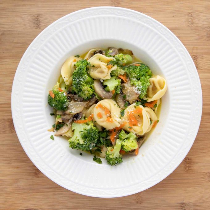tortellini and broccoli with broth in a white bowl