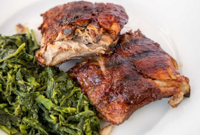 white plate with half rack of grilled baby back ribs cut in half and stacked, next to cooked broccoli rabe