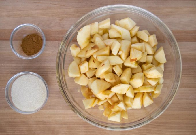 apples, sugar and cinnamon in bowls on a wooden cutting board