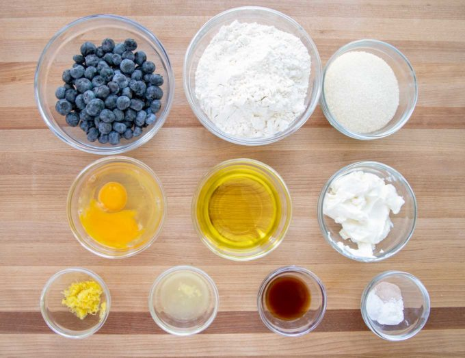 ingredients to make blueberry muffins in glass bowls on a wooden cutting board