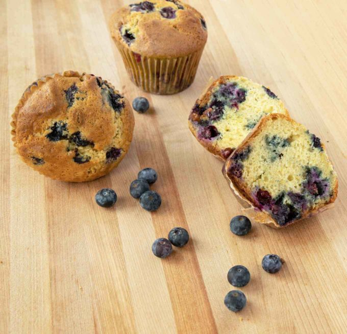 2 blueberry muffins and one muffin cut in half on a wooden cutting board with blueberries