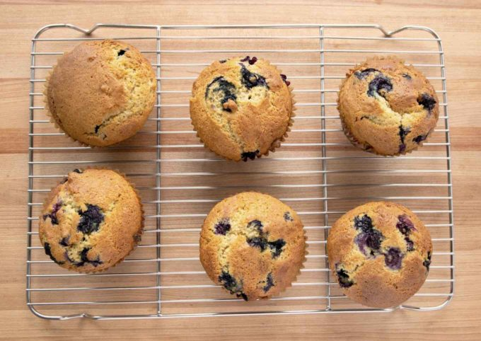 overhead view of 6 blueberry muffins on a wire rack sitting on a wooden cutting board