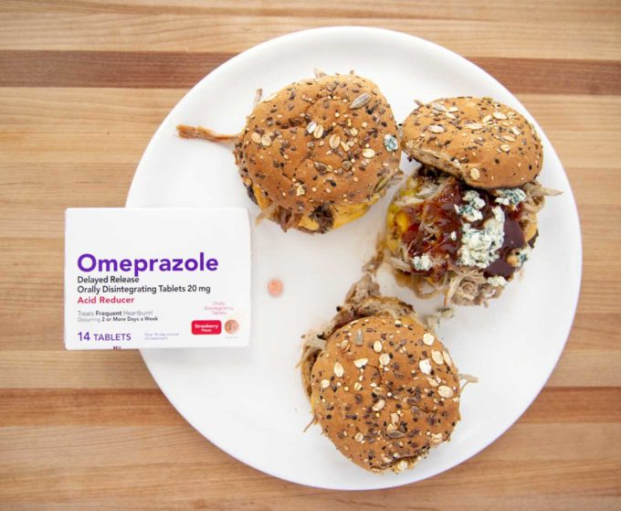 3 Cheeseburgers with pulled pork, barbecue sauce and blue cheese crumbles on seeded buns on a white platter with omeprazole ODT box and tablet