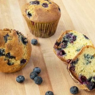 blueberry muffins with blueberries on a wooden cutting board