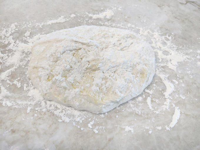 bread dough floured on a marble counter top