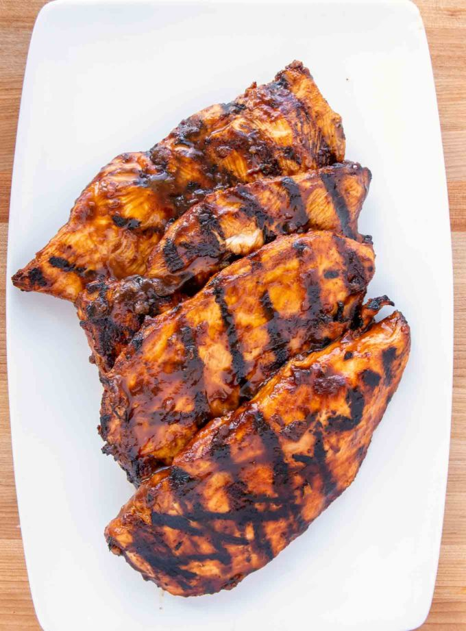 4 grilled chicken breasts with grill marks on a white platter