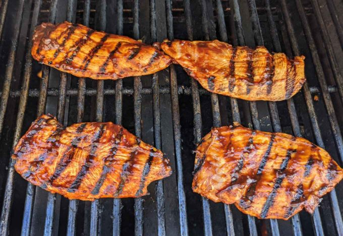 chicken breasts cooking on grill with grill marks on chicken