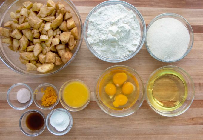 overhead view of the ingredients to make Jewish apple cake in glass bowls on a wooden cutting board