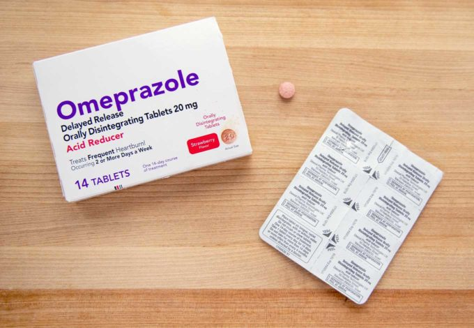 Omeprazole ODT box, package and pill on a wooden cutting board