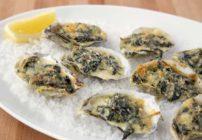 oysters rockefeller with a slice of lemon on a bed of rock salt on a white platter