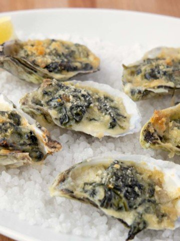 oysters rockefeller with a slice of lemon on a bed of rock salt on a white platter