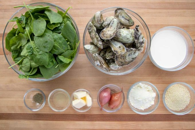 ingredients to make Oysters Rockefeller in glass bowls on a wooden cutting board