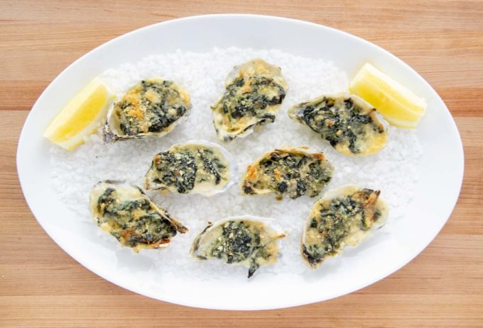 8 oysters rockefeller on a bed of rock salt with lemon slices  white oval platter