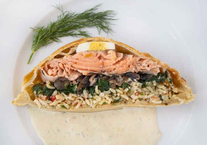 overhead view of a slice of Coulibiac of Salmon on a white plate with a dijon dill sauce and sprig of dill
