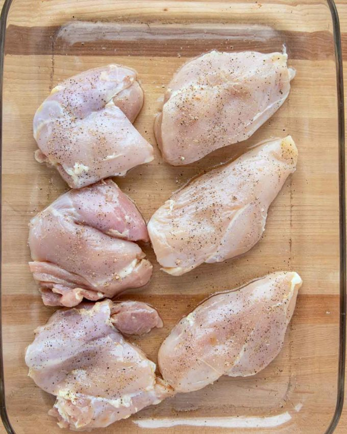 3 boneless skinless chicken breasts and 3 boneless skinless chicken thighs season with salt and pepper in a glass baking dish