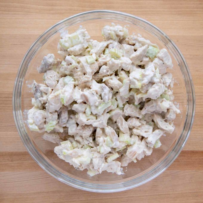 overhead view of chicken salad in a glass bowl on a wooden cutting board