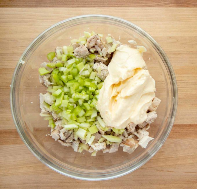 overhead view of chopped chicken, diced celery and mayonaise in a glass bowl on a wooden cutting board