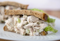 half of a chicken salad sandwich with lettuce on grain bread on a white plate