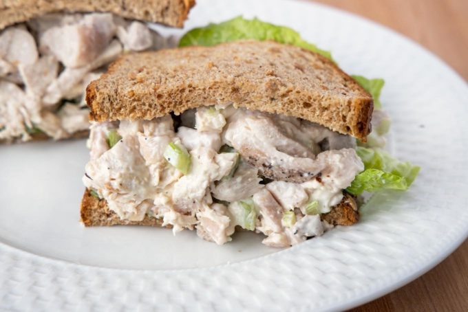 half of a chicken salad sandwich with lettuce on grain bread on a white plate with the other half behind it