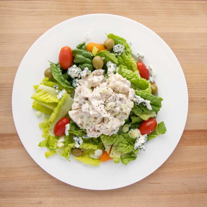 overhead view of salad on a white plate consisting of chopped romaine, grape tomatoes, green olives, gorgonzola cheese crumbles and big scoop of chicken salad in the middle
