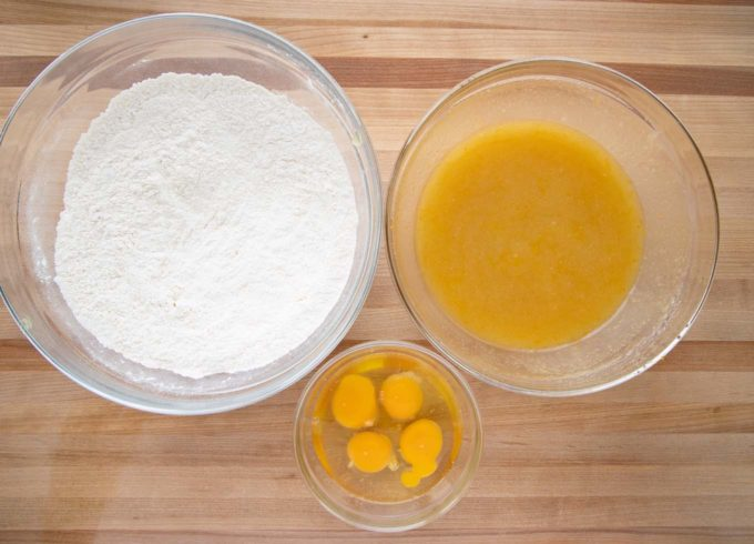 overhead view of a large bowl with flour mixture, a smaller bowl with oil, sugar mixture, a small bowl with eggs on a wooden cutting board