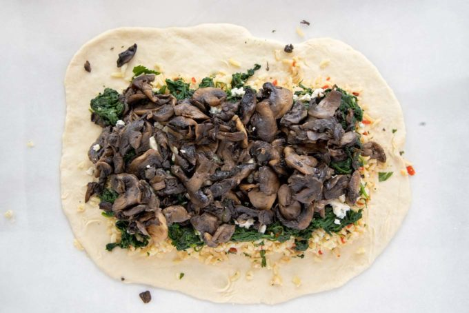 overhead view of mushrooms on top of spinach layer of coubilac