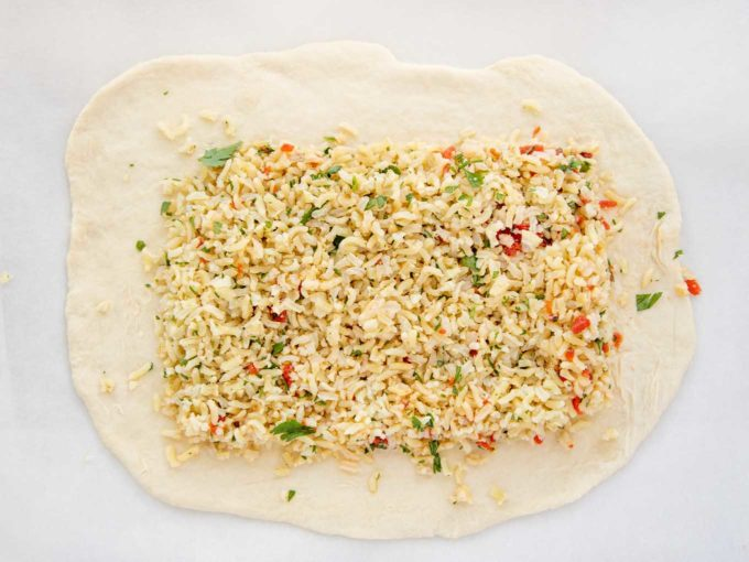 layer of rice seasoned with parsley and red pepper on a puff pastry sheet