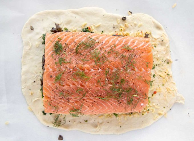overhead view of salmon seasoned with sea salt, pepper and dill on puff pastry sheet