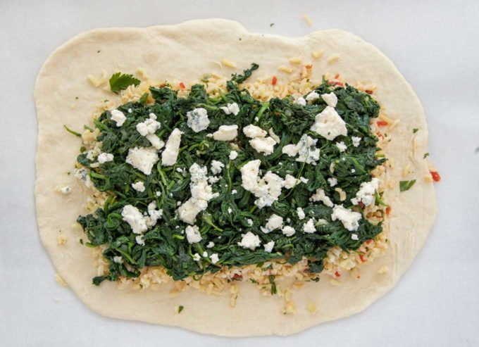 overhead view of puff dough with rice spinach and bleu cheese