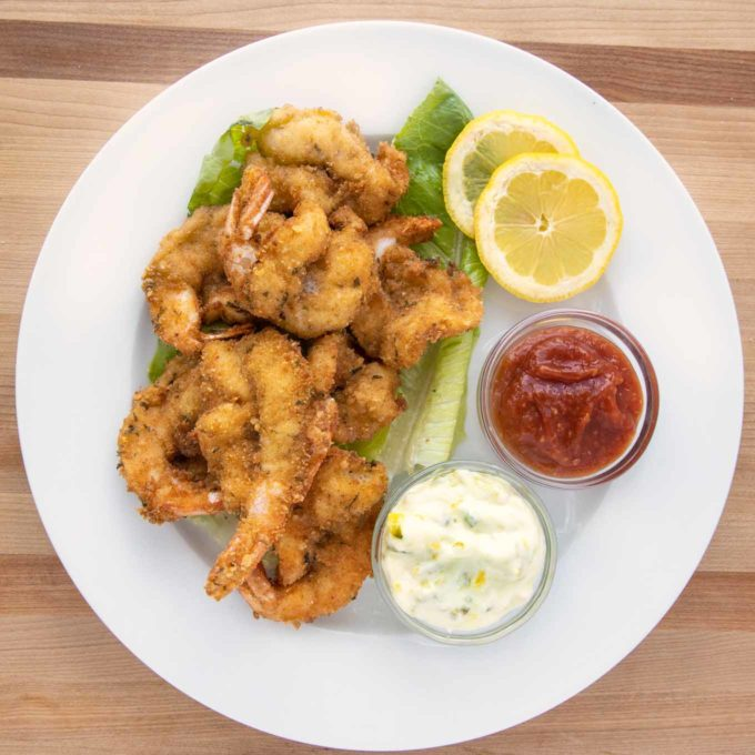 overhead view of golden brown fried shrimp on a white plate with tarter sauce, cocktail sauce and lemon slices