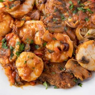 seafood sicilian served over a fried eggplant plank and linguine