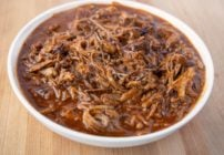 white bowl of pulled pork in barbecue sauce