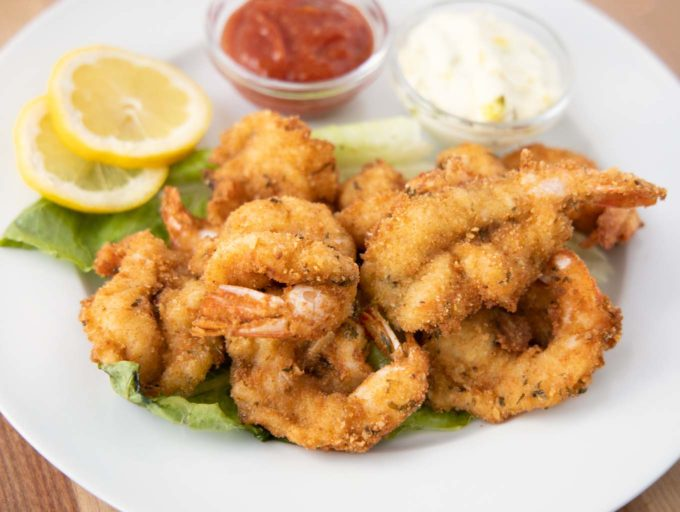 golden brown fried shrimp on a white plate with tartar sauce, cocktail sauce and lemon slices