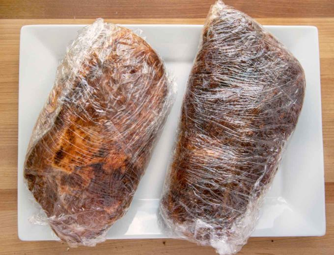 2 pork roasts coated with a dry rub and double wrapped in plastic wrap sitting on a white platter