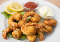 golden brown fried shrimp on a white plate with tarter sauce, cocktail sauce and lemon slices
