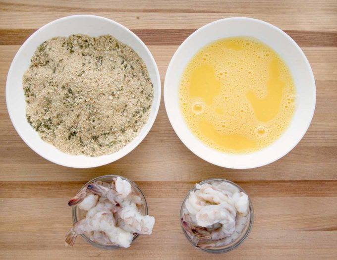 overhead view of raw shrimp and two white bowls with eggwash in one and seasoned bread crumbs in another