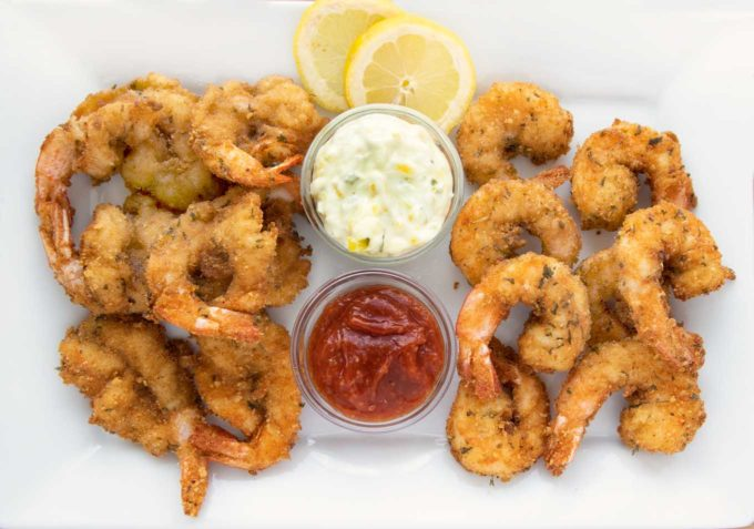 fried butterfly shrimp and fried regular shrimp on a white platter with tartar sauce, cocktail sauce and lemon slices
