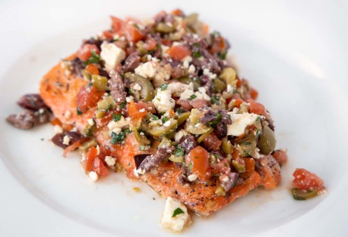 roasted salmon fillet topped with feta olive tapenade on a white plate