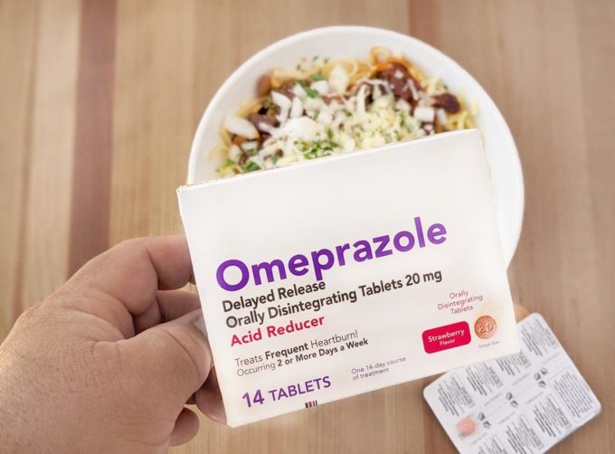 hand holding omeprazole ODT overtop of a bowl of cincinnati chili