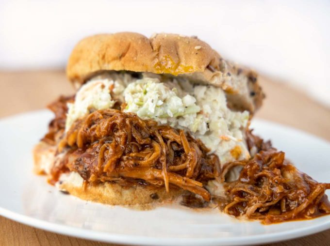 pulled pork topped with cole slaw on  seeded multigrain hamburger roll