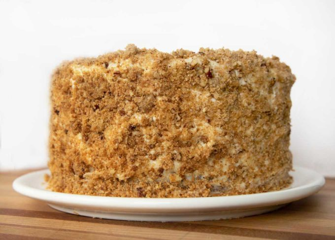 four layer banana crunch cake frosted and coated with crunch topping
