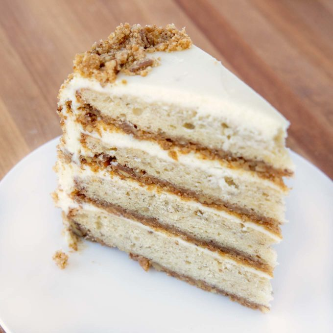 slice of four layer banana crunch cake on a white plate